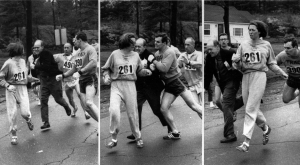 A woman, listed only as K. Switzer of Syracuse, found herself about to be thrown out of the normally all-male Boston Marathon when a husky companion, Thomas Miller of Syracuse, threw a block that tossed a race official out of the running instead, April 19, 1967 in Hopkinton, Mass.(AP PHOTO)